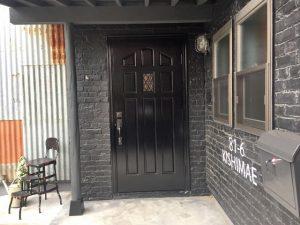 黒く艶めく木製ドアと黒レンガのデザインコンクリート。 「81-6 KASHIMAE」はハズせない Address。