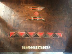 フロアの一部には遊び心。 木材フロア・タイル・アイアン文字のコラボレーション。